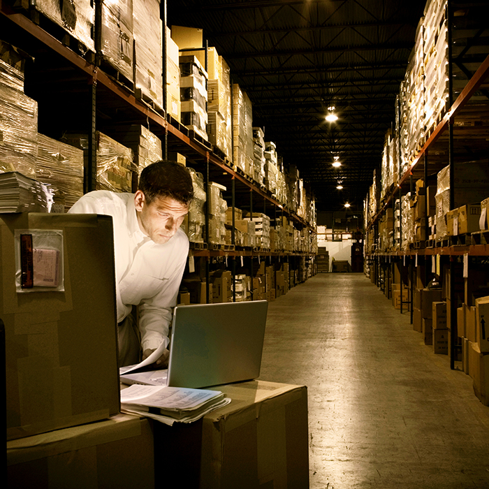 A worker on a laptop in a warehouse